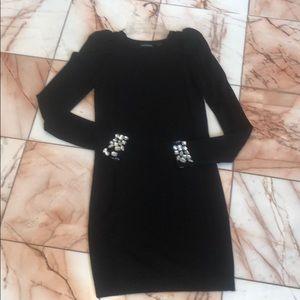 Black sweater dress with jewel cuffs.